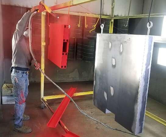 men applying powder coating to metal pieces
